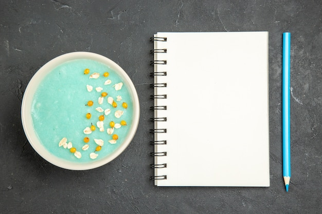 Top view blue iced dessert inside plate on dark floor cream ice color