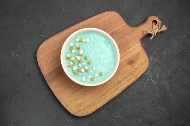 Dessert ghiacciato blu di vista superiore all'interno del piatto sulla crema di colore del gelato della tavola scura