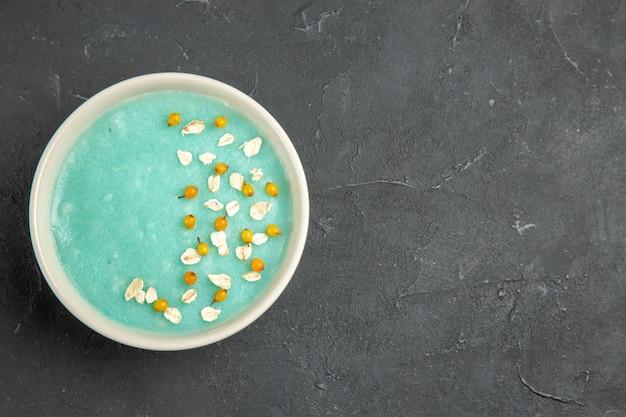 Вид сверху синий ледяной десерт внутри тарелки на темном столе кремового цвета льда