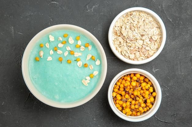 Dessert ghiacciato blu di vista superiore con muesli crudo sulla colazione scura della foto del gelato della crema della tavola