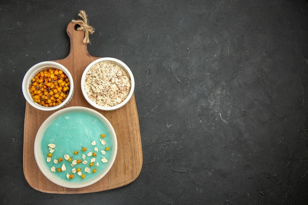 Top view blue iced dessert with raw muesli on a dark table ice color cream