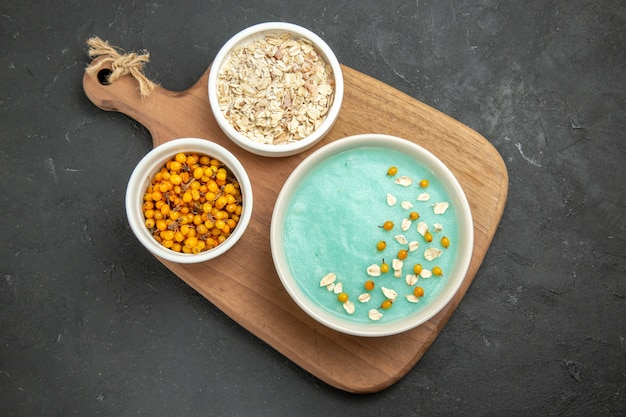 Dessert ghiacciato blu vista dall'alto con muesli crudo sulla crema color gelato tavolo scuro