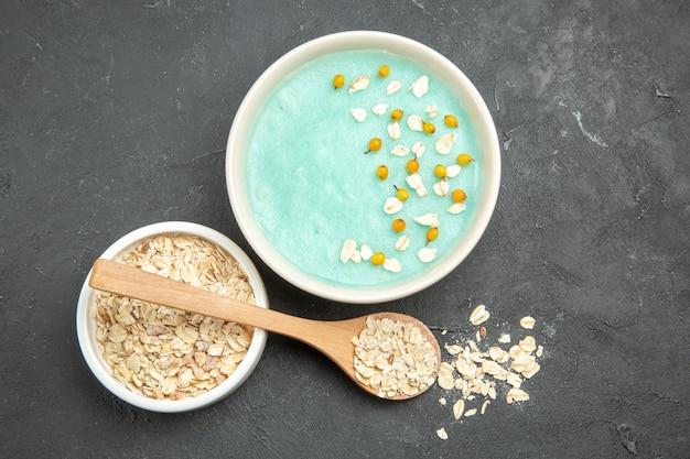 ダークテーブルの写真フルーツシリアルの朝食に生ミューズリーとトップビューの青いアイスデザート