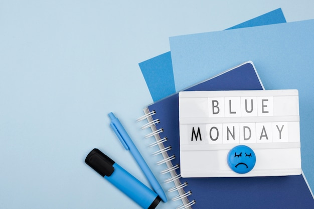 Top view of blue monday light box with sad face and marker