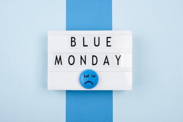 Vista dall'alto della scatola luminosa blu lunedì con la faccia triste