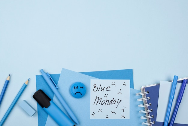 Top view of blue monday sad face with notebook and copy space