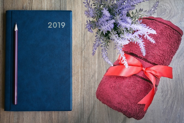 Top view of blue notebook with pencil, red towel and houseplant on wooden table.