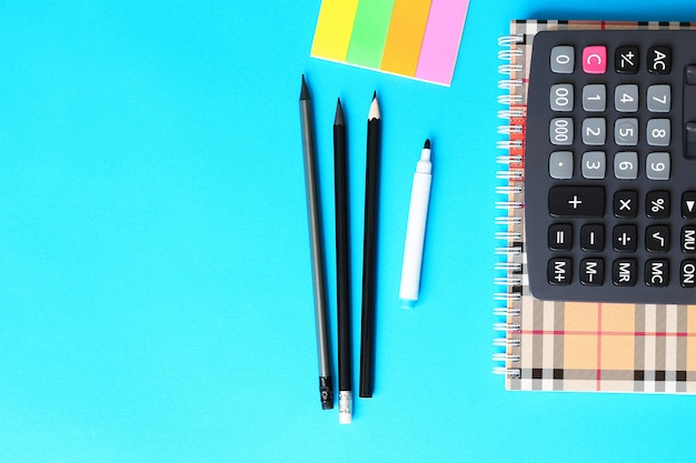 Top view of blue office desk with pencils, calculator and notebook. back to school concept.