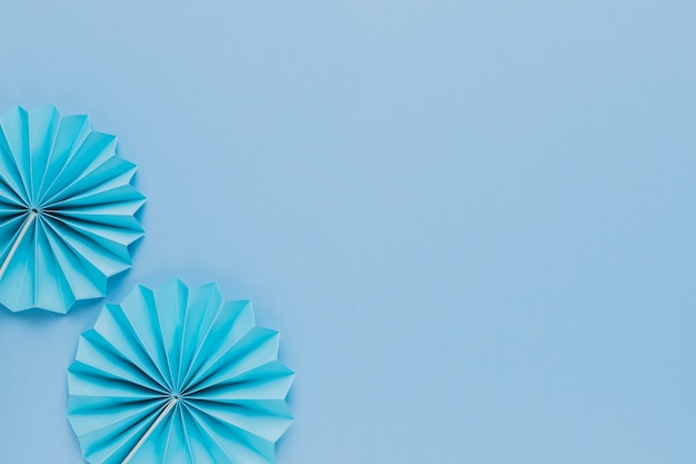 Top view of blue origami paper fan on plain background