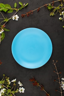 Top view blue plate empty around white flowers on the dark