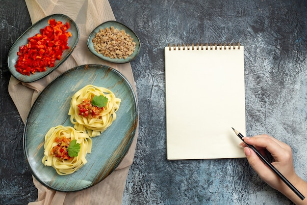 Top view of a blue plate with delicious pasta meal served with tomato and meat for dinner on tan color towel its ingredients hand holding a pen on spiral notebook