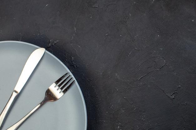 Вид сверху синяя тарелка с вилкой и ножом на темной поверхности