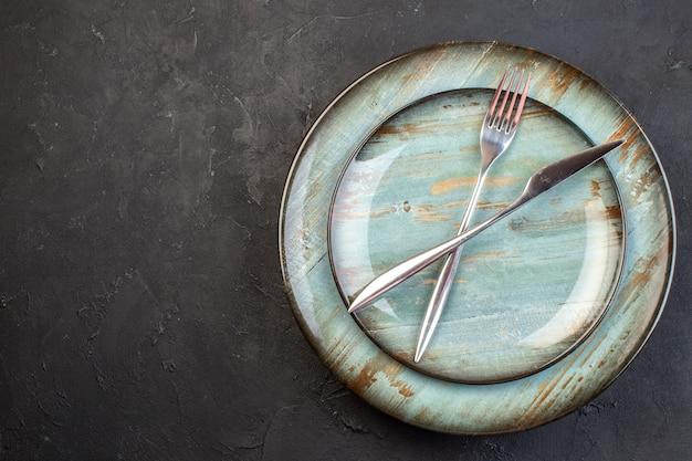 Piatto blu vista dall'alto con forchetta e coltello all'interno sulla superficie scura