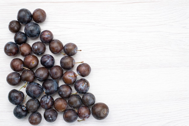 明るい背景に形成された丸い平面図の青いプラムジューシーなまろやかな酸味のフルーツ