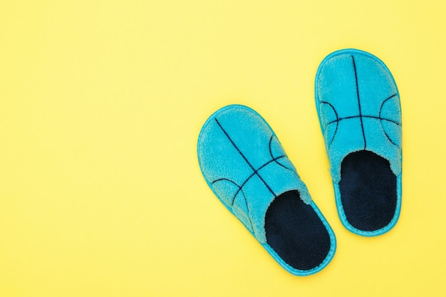 Top view of blue slippers on yellow background. comfortable home shoes. flat lay.
