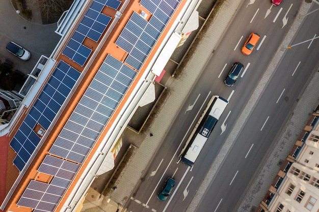 Top view of blue solar photo voltaic panels system on high apartment building roof top on sunny day. renewable ecological green energy production concept.