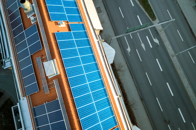 Top view of blue solar photo voltaic panels system on high apartment building roof top on sunny day. renewable ecological green energy production .