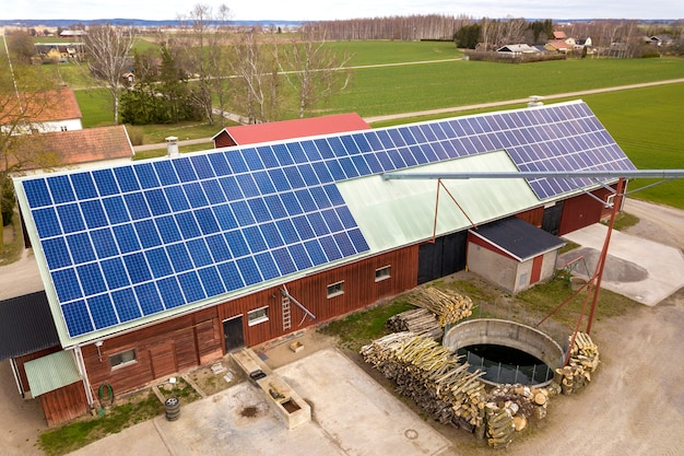 Top view of blue solar photo voltaic panels system on wooden building, barn or house roof. renewable ecological green energy production concept.