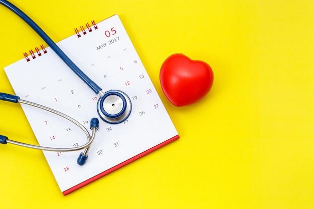 Вид сверху синий стетоскоп на белом календаре