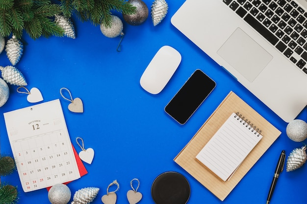 Top view of a blue table with laptop and christmas decor