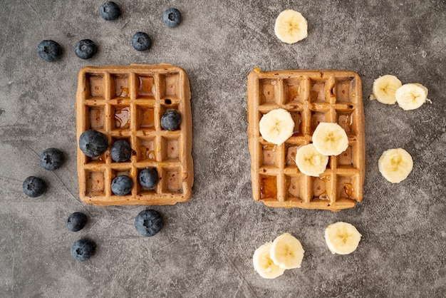 Top view of blueberries and banana slices on top if waffles