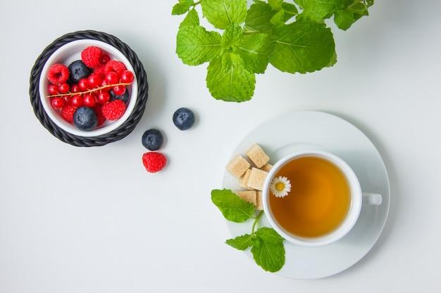 Vista dall'alto mirtilli e lamponi in una ciotola con ribes rosso, camomilla, zucchero, foglie di menta.