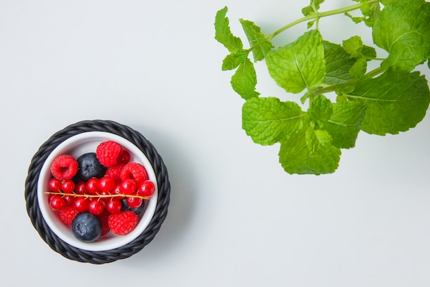 Top view blueberries and raspberries in bowl with redcurrant, mint leaves.