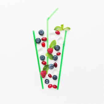 Top view of blueberries in straw glass with mint