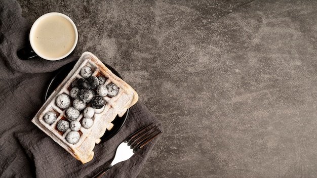 Top view of blueberries on waffles covered in powdered sugar
