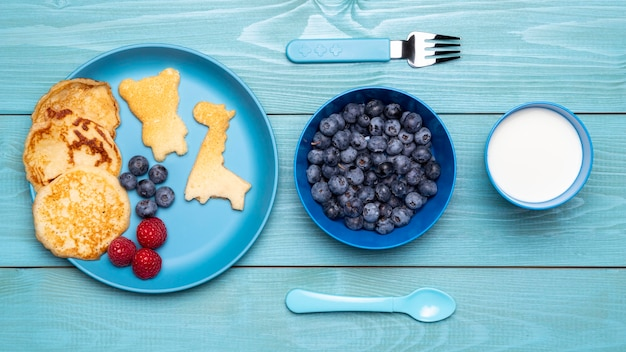 Top view of blueberries with baby food and cutlery