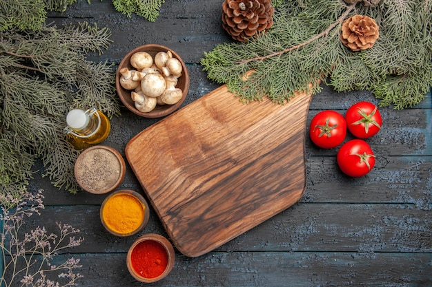 Top view board and spices wooden brown cutting board next to three tomatoes and different colorful spices under oil in bottle branches and bowl of mushrooms