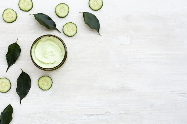 Top view of body butter and cucumber on wooden table