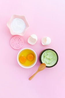 Top view of body butter and eggs on pink background