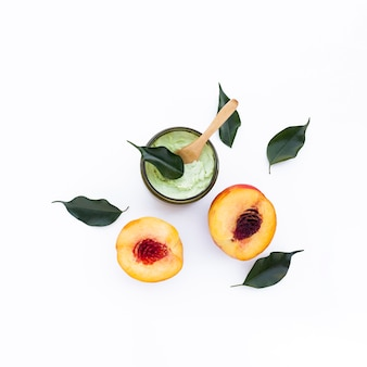 Top view of body butter and nectarines on white background
