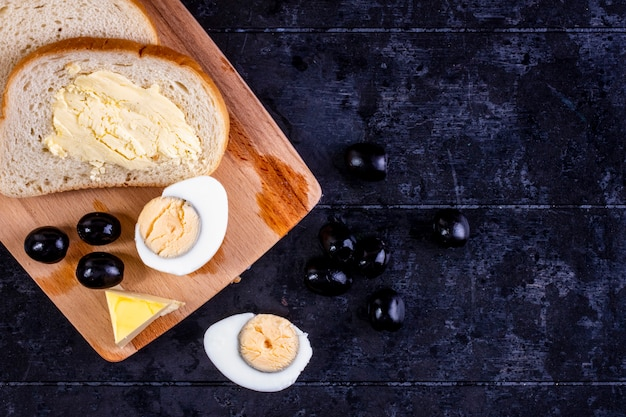 Top view boiled egg on a board with olives and slices of bread and butter on a black wall
