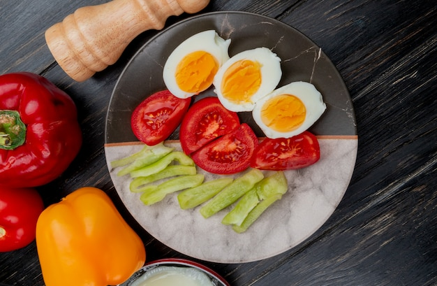 Top view of boiled eggs on a plate with tomato slices and colorful bell peppers on wooden background