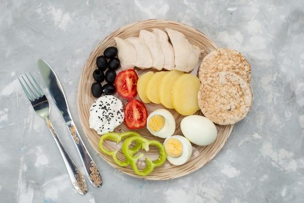 トップビューゆで卵とオリーブの胸肉の調味料とトマトの灰色、野菜料理の食事の朝食