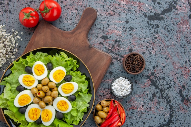 Top view boiled eggs with seasonings and red tomatoes on light background