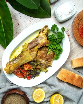 Top view boiled lamb leg with vegetables with spices lemon slices and bread