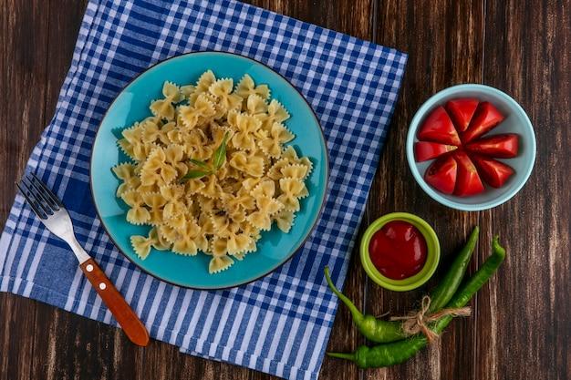 Vista dall'alto di pasta bollita su una piastra blu su un asciugamano a scacchi blu con una forcella pomodori ketchup e peperoncino su una superficie di legno