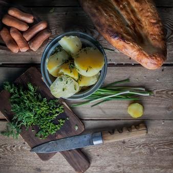 Vista dall'alto patate bollite con cipolle verdi e pane e coltello nel tavolo