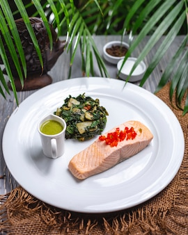 Top view boiled red fish with stew greens and sauce on a plate