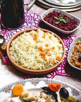 Вид сверху отварной рис на тарелке с отварным картофелем и тыквой
