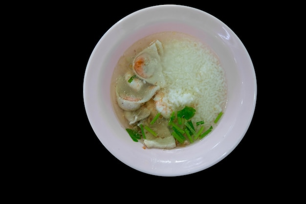 Top view of boiled rice soup with seafood (shrimps, squid and fish).