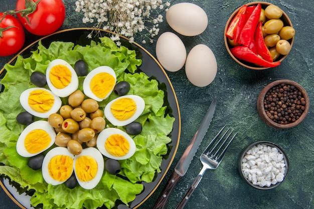 Вид сверху вареные нарезанные яйца с зеленым салатом и оливками на темном фоне