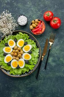 Вид сверху вареные нарезанные яйца с зеленым салатом и оливками на темно-синем фоне