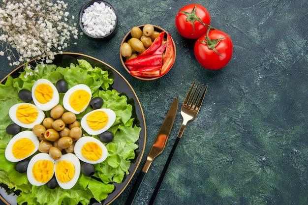 紺色の背景にグリーンサラダとオリーブと茹でたスライス卵の上面図