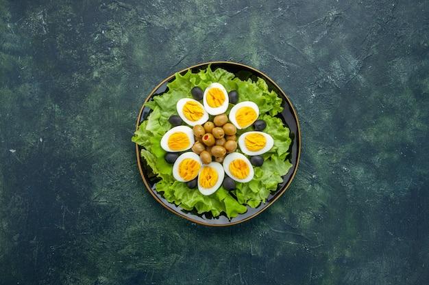 Вид сверху вареные нарезанные яйца с оливками и зеленым салатом на темном фоне