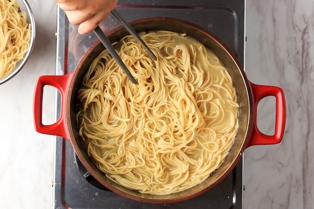 Вид сверху: варка корейской лапши быстрого приготовления или пасты для спагетти на красной сковороде, домашняя кулинария