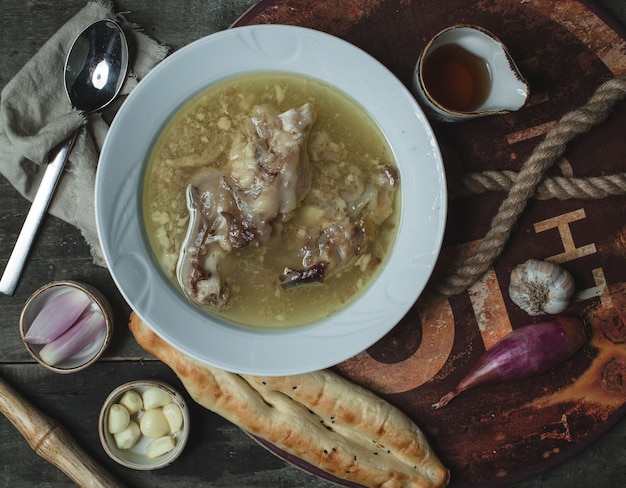 Top view bone broth soup, khash served with garlic and vinegar